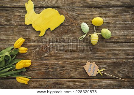 Top View Of Flowers, Yellow Rabbit And Four Dyed Eggs On The Wooden Panel