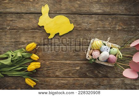 Top View Of Bouquet Of Tulips, Wooden Bunny And Colored Eggs On Ligneous Surface