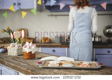Calm Woman Standing With His Back At The Stove And Preparing Dinner For Holiday. Focus On Food On Th