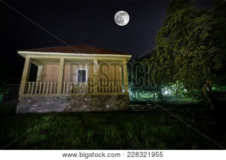 Mountain Night Landscape Of Building At Forest In Foggy Night With Moon. Green Meadow, Big Trees And