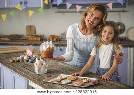 Portrait Of Happy Mother And Daughter Standing In The Cuisine And Showing Homemade Easter Pastry. Co