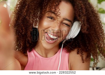 Close Up Shot Of Cheerful African American Female Listens Pleasant Music With Headphones, Poses For