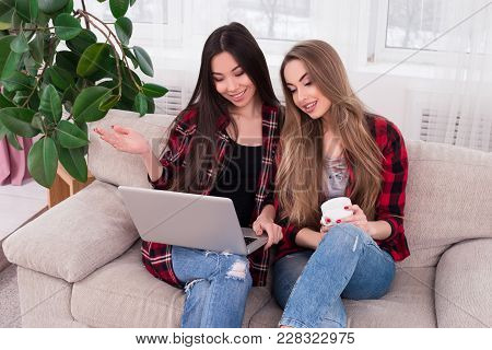 Be Cheerful With Friends! Two Young Good-looking Smart Girls Sitting On The Beige Sofa And Chilling