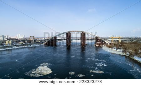 Rusty unfinished bridge in Kiev, Ukraine. Combined car and subway bridge under construction. Mounting of steel arch. Unfinished Podolskyi bridge. poster