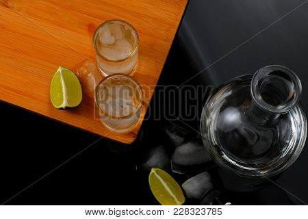 Two Shots With Alcohol Near The Decanter. Two Shots With Strong Alcohol On A Brown Board Made Of Woo