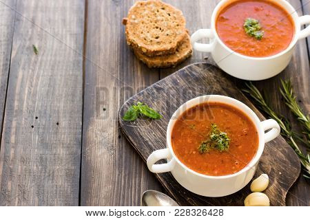 Thick Italian Soup Minestrone With Pesto Sauce On A Wooden Table