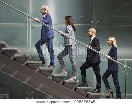 Multinational And Multiethnic Corporate Business People Male And Female Walking Up Stairs In A Line