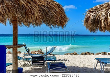 Sunbeds And Parasol Against The Crystal Sea Water In Eagle Beach, Aruba. Caribbean Landscape.