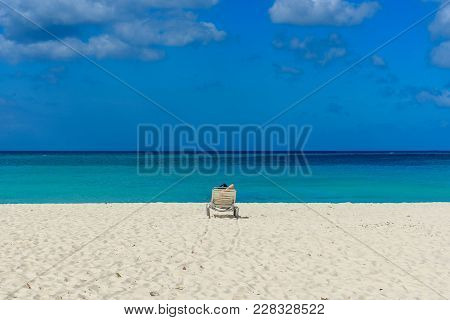 A Person Tans On A Sunbed On The Shore Of The Caribbean Sea Of Eagle Beach, Aruba
