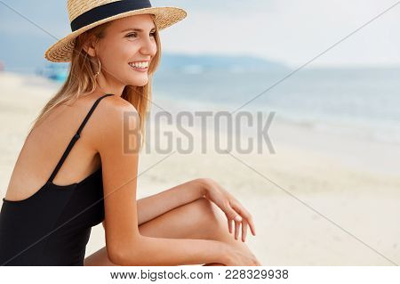 Adorable Young Woman Wears Straw Hat, Sits On Desert Seashore Alone, Faces Blue Calm Water, Remember