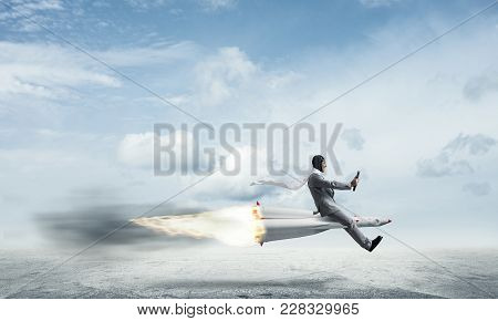 Conceptual Image Of Young Businessman In Suit Flying On Rocket Above Asphalt Road With Blue Cloudy S