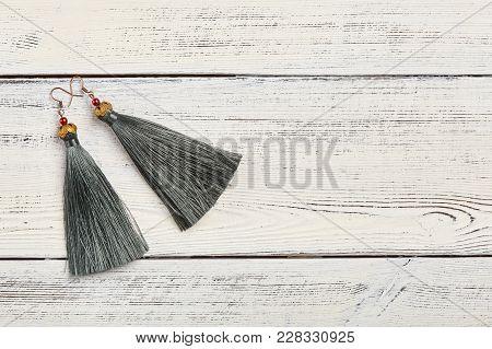 Gray Tassel Earrings On White Background, Copy Space