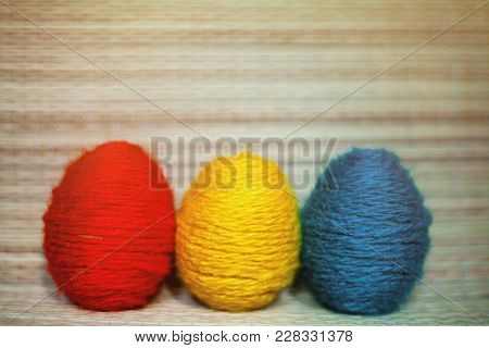 Red, Yellow And Green Eggs In The Straw Background. Eggs Are Threaded In Colored Thread