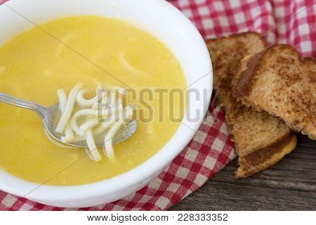 Horizontal Image Of A White Glass Bowl Of Chicken Noodle Soup Adorned With A Sandwhich Sitting On A