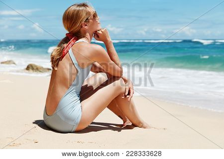 Back View Of Thoughtful Female Contemplates While Sits On Sand Near Ocean, Wears Blue Bikini And Sun