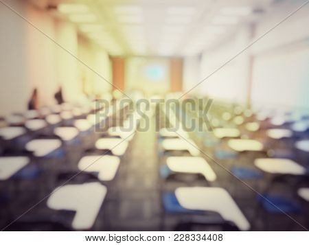 Blurred Image Of Empty Large Examination Room With Wooden Chairs Style. No People