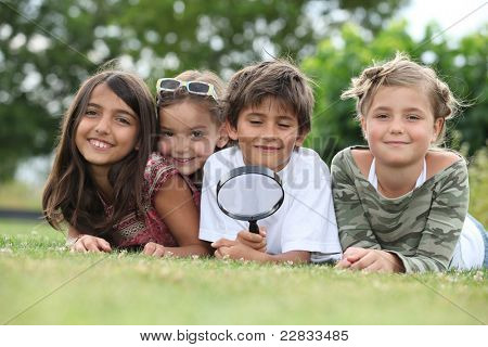 Kids playing with magnifying glass in park
