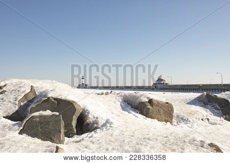 Lighthouses On Frozen Lake Superior Waterfront, Duluth, Minnesota In Winter  On Frozen Rocky Shores