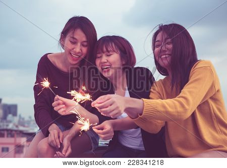 Happy Group Of Asia Girl Friends Enjoy And Play Sparkler At Roof Top Party At Evening Sunset,holiday