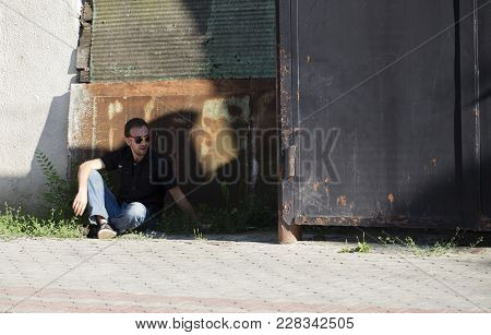 Man And A City. The Tramp Is Siting In The Shadows Near Old Shed.