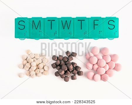 Top View Of Seven Day Pill Box And Heap Of Pills. Green Pill-box And Pills Isolated On White. Pill B