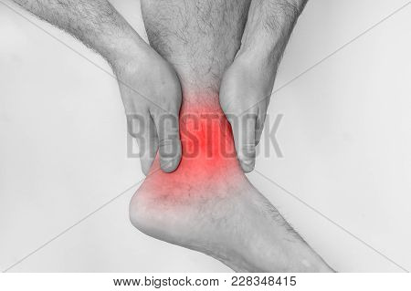 Man With Ankle Pain Holding His Aching Leg - Black And White Photo