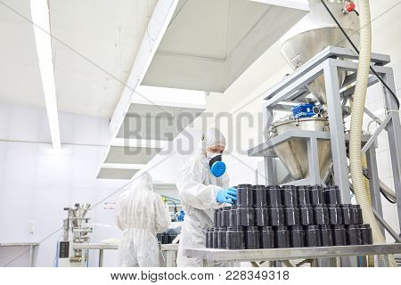 Two Pharmaceutical Factory Workers Wearing Coveralls And Respirators Wrapped Up In Preparations For