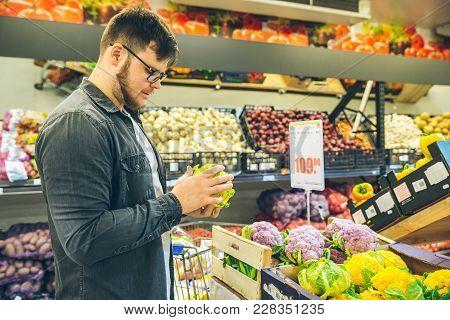 Man Seek Vegetables In Supermarket Stand Near Shelf With Cabbage