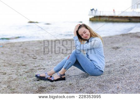 Smiling Young Woman Rests On Beach And Poses In Camera, Sitting