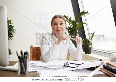 Attractive Experienced 50 Year Woman Chief Architect With Gray Hair Studying Drawings On Desk In Fro