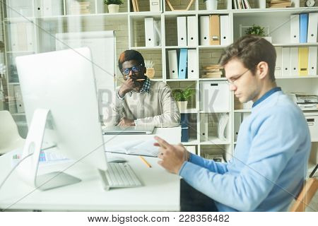Working Process In Modern Open Plan Office: Multi-ethnic Team Of White Collar Workers Sitting At Des
