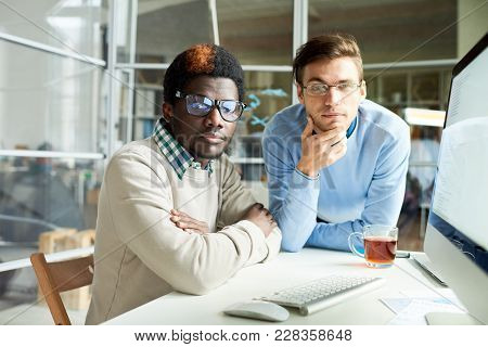 Multi-ethnic Team Of White Collar Workers Wearing Eyeglasses Looking At Camera While Gathered Togeth