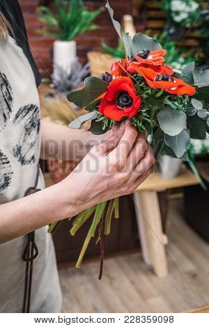 Faceless Woman Holding Floral Arrangement With Bright Red Poppy Flowers.