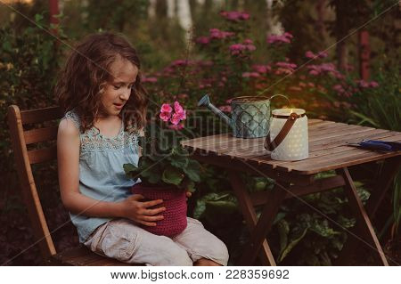 Dreamy Romantic Kid Girl Relaxing In Evening Summer Garden Decorated With Lantern And Candle Holder