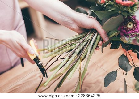 Crop Shot Of Woman Cutting Stems Of Green Flowers Composed In Bouquet Working In Shop.