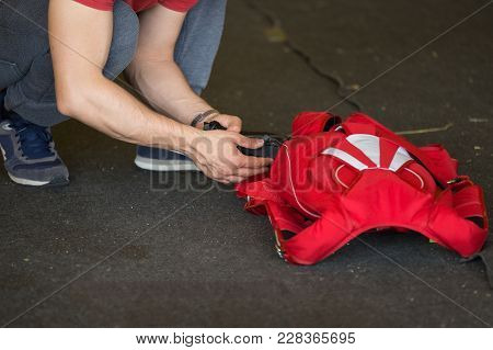Skydiver Packing His Red Parachute In The Aerodrome Room