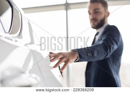 Portrait Of Handsome Businessman Gently Touching Smooth Metal Of White Luxury Car, Focus On Foregrou