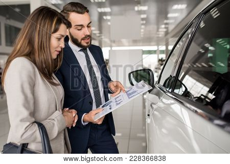 Side View Portrait Of Modern Young Woman Listening To Car Dealer While Choosing Luxury Car In Showro