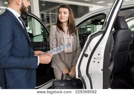 Portrait Of Beautiful Modern Woman Listening To Car Salesman Standing By Expensive Luxury Car In Sho