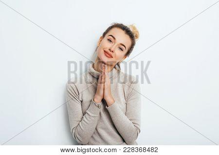 Horizontal Portrait Of Pretty Woman Keeps Palm Together, Has Pleased Expression, Begging Asks Boyfri