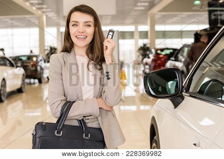 Portrait Of Beautiful Young Woman Holding Car Keys And Smiling Cheerfully At Camera Standing In Luxu
