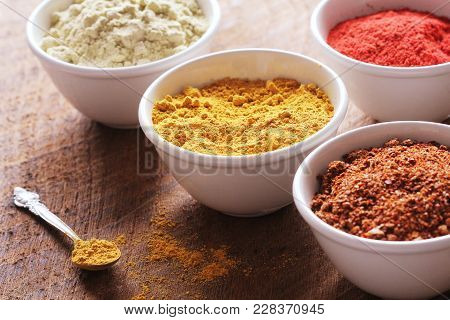 Various Colorful Spices On Wooden Table In Bowls . Food And Cuisine Ingredients