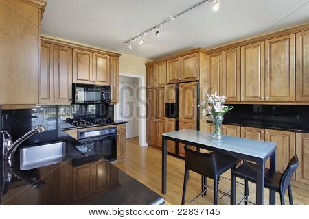Kitchen in condominium with oak wood cabinetry