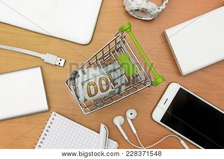 A Small Shopping Trolley With Money, Gadgets On A Wooden Table Top View. Online Shopping Concepts