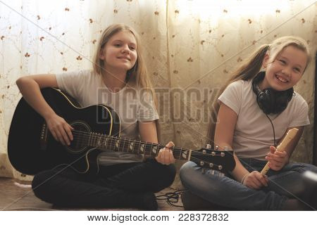 Two Female Teens Playing Musical Instruments At Home, Youth Hobby And Leisure Concept