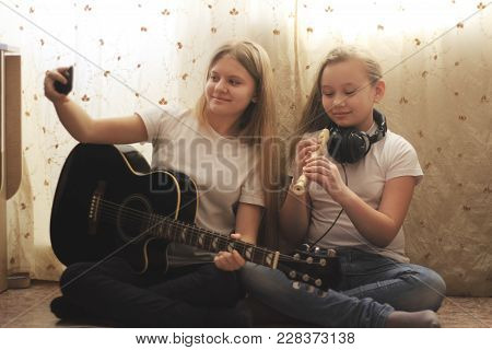 Two Female Teens Playing Musical Instruments And Making Selfie Sitting On The Floor At Home, Youth H