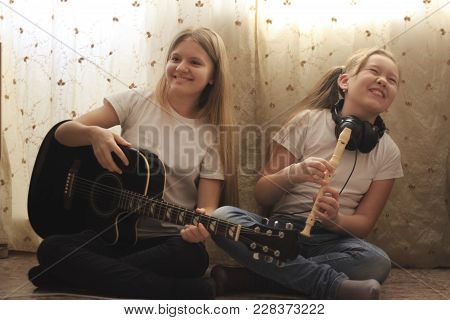 Two Female Teens With Smartphone And Musical Instruments Sitting On The Floor At Home, Youth Hobby A