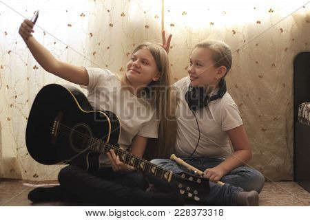 Two Female Teens Making Selfie And Posing With Musical Instruments Sitting On The Floor At Home, You