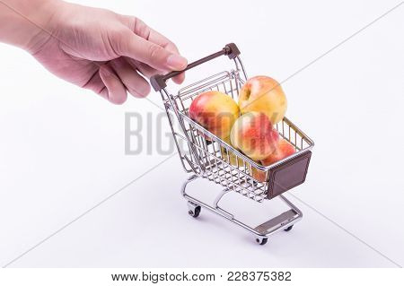 A Shopping Cart With Fruits Inside With Hands Pushing The Cart Isolated Over White Background