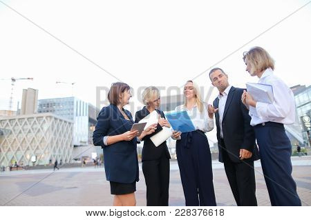 Members Of Business Organization Talking Outside And Smiling With Document Case And Tablet In Hands.
